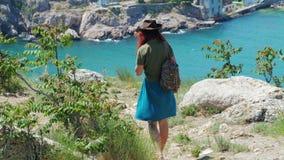 Het mooie roodharige meisje in een cowboyhoed loopt door de bergen door het overzees stock videobeelden