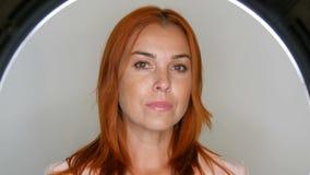 Het mooie roodharige volwassen vrouwelijke model stellen op middelbare leeftijd voor de camera in studio stock footage