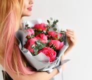 Het mooie rustieke boeket van de vrouwengreep van roze pioenen bloeit het gelukkige glimlachen op grijs Stock Afbeelding