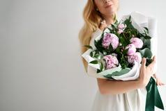 Het mooie rustieke boeket van de vrouwengreep van roze pioenen bloeit het gelukkige glimlachen op grijs Royalty-vrije Stock Foto