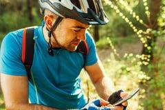 Het mooie schot van fietser op fiets die navigator op zijn apparaat gebruiken, onderzoekt kaart en onderzoeks de coördinaten van  royalty-vrije stock foto