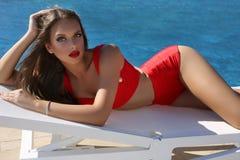 Het mooie sensuele meisje met blond haar draagt luxueus rood zwempak Royalty-vrije Stock Foto's
