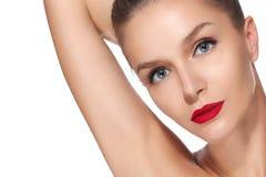 Het mooie donkerbruine meisje met de perfecte rode lippenstift van huid blauwe ogen op een witte achtergrond hief omhoog haa Royalty-vrije Stock Foto's