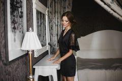 Het mooie, sexy en modieuze donkerbruine modelmeisje met heldere make-up in korte zwarte satijnpeignoir kijkt beneden binnen en s Stock Afbeelding