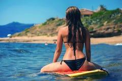 Het mooie jonge meisje die van de vrouwensurfer op een golf wachten Royalty-vrije Stock Foto's