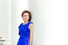 Het mooie sexy jonge meisje in een blauwe kleding met een mooie kapsel en een make-up bevindt zich op straat in stads rode schoen Stock Foto's