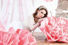 Het mooie sexy meisje in een lange kleding met reusachtige roze bloemen zit Royalty-vrije Stock Fotografie