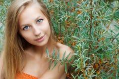 Het mooie sexy meisje met groot lippen lang haar met donkere huid zit dichtbij de duindoornzomer op een warme Zonnige dag Stock Afbeeldingen