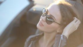 Het mooie sexy meisje met lang haar in een leerjasje en leerbroek in zonnebril zit in cabriolet stock footage