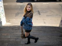 Het mooie slanke blondemeisje bevindt zich op de treden op de straat met een in hand rugzak royalty-vrije stock fotografie