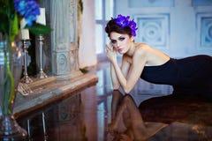 Het mooie slanke brunette ligt op de vloer door open haardne Stock Afbeeldingen