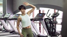 Het mooie slanke jonge vrouwelijke geschiktheid model het doen opwarmen in de gymnastiek stock footage