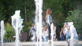 Het mooie slanke meisje met lang haar berijdt een gyroscoop in het park voorbij de fonteinen en de mensen stock footage