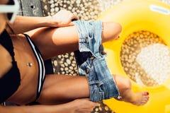 Het mooie slanke meisje in sexy gestreepte bikini trekt van haar borrels Stock Fotografie