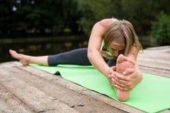 Het mooie slanke meisje voert een yoga uit stelt stock afbeelding