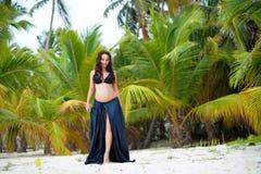 Het mooie slanke zwangere meisje gaat naar zandig strand Tropische aard, palmen Royalty-vrije Stock Foto's