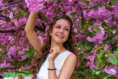 Het mooie smily meisje met krullend haar in witte kleding in de tuin in roze bloesem bloeit stock afbeeldingen