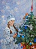 Het mooie sneeuwmeisje verfraait een Kerstboom Nieuwe jaar en Kerstmis royalty-vrije stock foto's