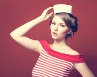 Het mooie speld-omhooggaande meisje kleedde zeeman het stellen op rode achtergrond Royalty-vrije Stock Afbeeldingen