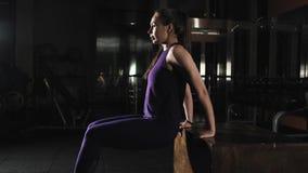 Het mooie sportenmeisje is bezig geweest met fitness Het doen van oefening voor triceps met een bank stock videobeelden