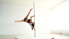 Het mooie sportenmeisje leidt op een pyloon op Witte lichte ruimte en slanke atleet in zwarte borrels en bovenkant stock footage