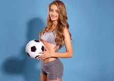 Het mooie sportenmeisje stellen met een bal als voetbalster op een blauwe achtergrond Stock Fotografie