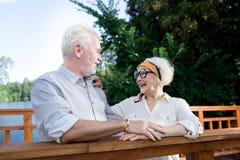 Het mooie teruggetrokken vrouw lachen die aan grappen van haar echtgenoot luisteren stock fotografie