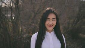 Het mooie Thaise meisje bekijkt camera en glimlacht cutely Gelukkig en vriendelijke tiener stock videobeelden
