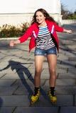 Het mooie tiener rollerskating in park Royalty-vrije Stock Afbeeldingen
