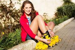 Het mooie tiener rollerskating in park Stock Foto