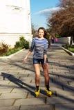 Het mooie tiener rollerskating in park Stock Foto's