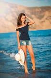 Het mooie tienermeisje gaat op kust van oceaan met strohoed in handen Stock Fotografie