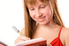 Het mooie tienermeisje glimlachen, die nota's neerschrijft Stock Fotografie