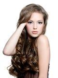 Het mooie tienermeisje met lange krullende haren, dient haar haar in Royalty-vrije Stock Foto