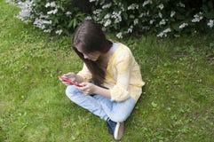 Het mooie tienermeisje met tabletcomputer zit op het Gras in Park foto Royalty-vrije Stock Foto's