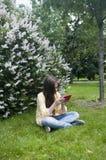 Het mooie tienermeisje met tabletcomputer zit op het Gras in Park foto Royalty-vrije Stock Foto