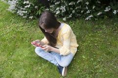 Het mooie tienermeisje met tabletcomputer zit op het Gras in Park foto Stock Afbeelding