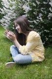 Het mooie tienermeisje met tabletcomputer zit op het Gras in Park foto Royalty-vrije Stock Afbeeldingen