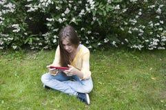 Het mooie tienermeisje met tabletcomputer zit op het Gras in Park foto Royalty-vrije Stock Fotografie