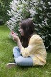 Het mooie tienermeisje met tabletcomputer zit op het Gras in Park foto Stock Afbeeldingen