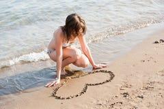 Het mooie tienermeisje trekt liefdevorm op zand Royalty-vrije Stock Foto's