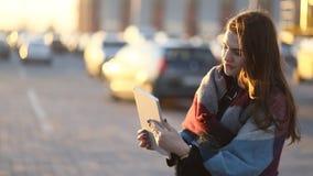 Het mooie toungmeisje model communiceren met iemand door het stootkussen in de stedelijke zonnige straat stock videobeelden