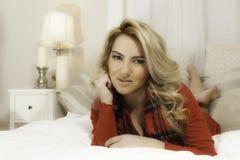 Het mooie van Kerstmiskleren van het Blondemeisje Rode Bed Chin On Hand Royalty-vrije Stock Fotografie