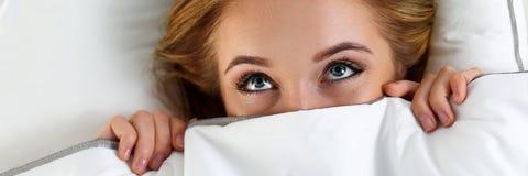 Het mooie verbergende gezicht van de blondevrouw onder dekking die in bed liggen stock foto's