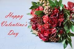 Het mooie verse bloemstuk van rode rozen en de tekst wensen, het concept van de de groetkaart van de Valentijnskaartendag dit stock fotografie