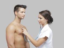 Het mooie volwassen arts onderzoeken mensen Stock Afbeeldingen
