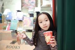 Het mooie vrolijke meisje eet roomijs royalty-vrije stock afbeelding