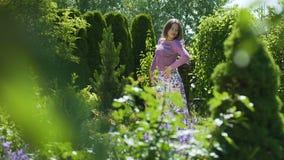 Het mooie vrouw dansen in groene tuin langzame motie, geniet zich van vrij bewegen zich stock footage