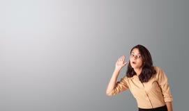Het mooie vrouw gesturing met exemplaarruimte Stock Foto