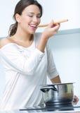 Het mooie vrouw koken bij de keuken stock afbeeldingen